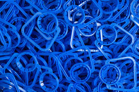 Background of new blue plastic handles for easy carrying of plastic liquid containers.