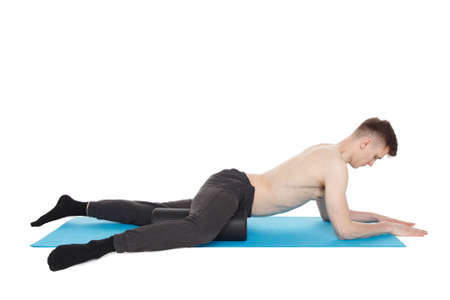 Handsome man shows exercises using a foam roller for a myofascial release massage of trigger points. Massage of the inner thigh muscle. Isolated on white.