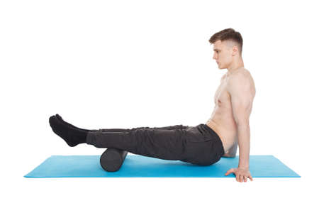 Handsome man shows exercises using a foam roller for a myofascial release massage of trigger points. Massage of the shin muscle. Isolated on white.