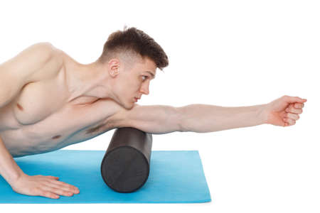 Handsome man shows exercises using a foam roller for a myofascial release massage of trigger points. Massage of the triceps muscle. Isolated on white. Imagens