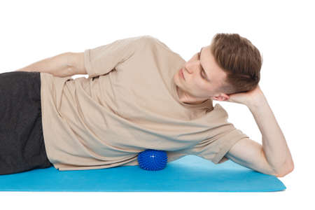Handsome man shows exercises using the ball with spikes for a myofascial release massage of trigger points. Massage of the broadest back muscle. Isolated on white. Stock fotó