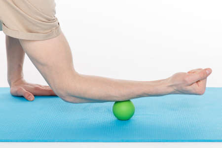 Handsome man shows exercises using the ball for a myofascial release massage of trigger points. Massage of the triceps muscle. Isolated on white.