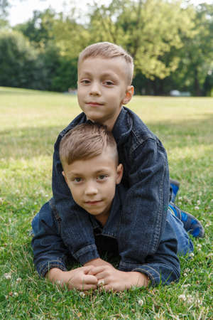 Two boys of three years in jeans are laying on the grass and hugging. Two close friends, two cousins. Family relations between brothers Foto de archivo