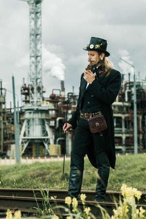 Young man weared in steampunk style posing on industrial background