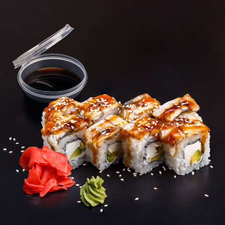 Traditional delicious fresh Unagi sushi roll set on a black background with reflection. Sushi roll with rice, nori, eel,, cream cheese, avocado, unagi sauce. Sushi menu. Japanese kitchen.