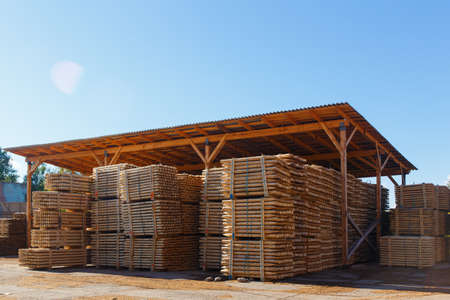 Piles of wooden boards in the sawmill, planking. Warehouse for sawing boards on a sawmill outdoors. Wood timber stack of wooden blanks construction material. Lumber Industry. Stock Photo