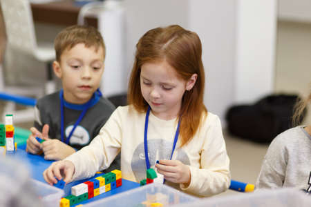 Grodno, Belarus - January 13, 2019: Children collect various objects from plastic parts of the constructor at the school of digital technologies Foresight. Their work is controlled by the teacher. Editoriali