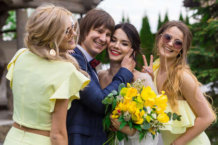 Newly married with bridesmaids on wedding ceremony posing at the villa