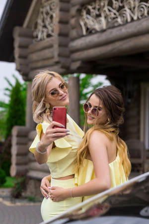 Portrait of two pretty young bridesmaids in yellow dresses near by a fashionable wooden house. People lifestyle concept. Doing selfie shot on mobile phone smiling and sending air kiss