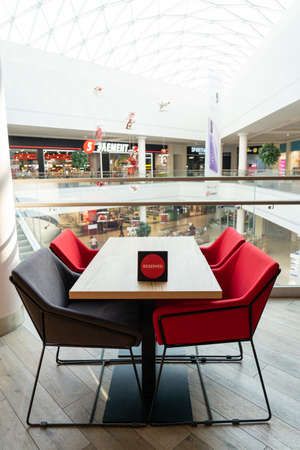A table and soft chairs for visitors to the food court of a modern shopping center. The table is reserved. Stock fotó