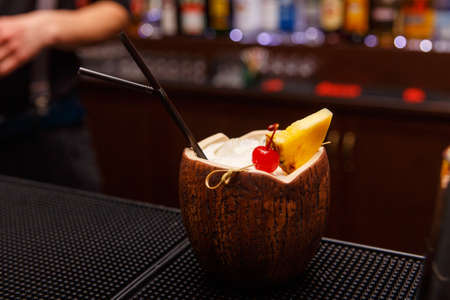 Exotic alcoholic cocktail in coconut standing on bar tender.