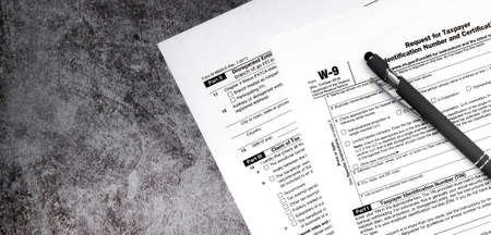 Tax relief and tax forms with a signature pen on a gray background