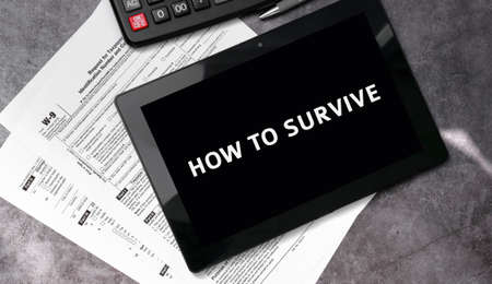 How to survive on a black tablet and with tax forms and calculator 免版税图像