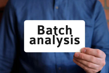 Batch analysis text on a white sign in the hand of a man in a blue shirt