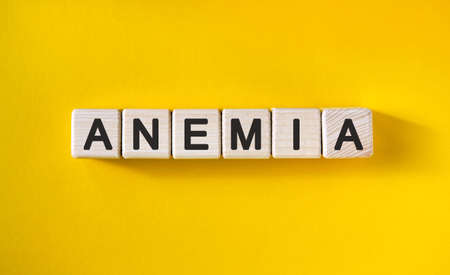 Anemia - text on wooden cubes and yellow background Stock Photo