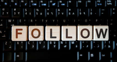Follow - concept text on wooden cubes on background black keyboard