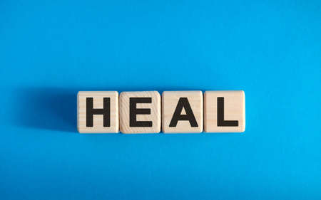 HEAL - text on wooden blocks, medical concept, blue background