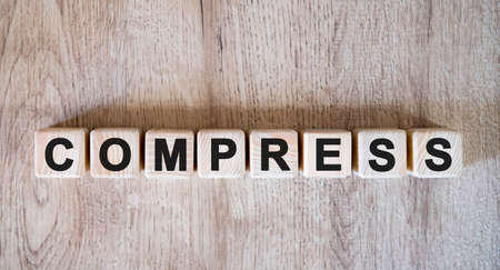 COMPRESS text word on wooden cubes on wooden background