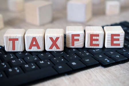Tax and Fee text on cubes lying on the keyboard Stock fotó - 151945350