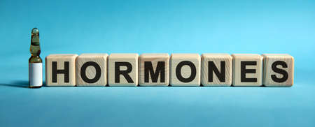 HORMONES - word on cubes. Drug in ambula to reduce disease symptoms on a blue background Stock Photo