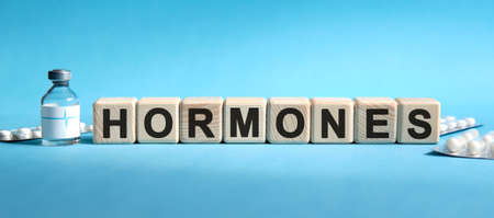 HORMONES - text on cubes. Drug in ambula, tablets in blisters to reduce disease symptoms