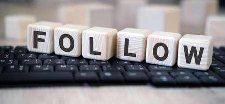 Follow - text cubes stand on a black keyboard on a wooden table Foto de archivo