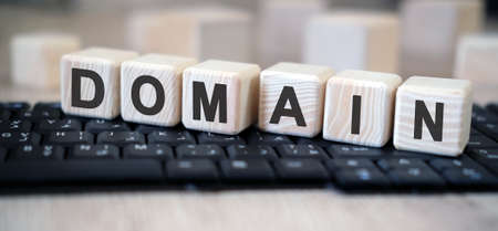 Domain - text cubes stand on a black keyboard on a wooden table