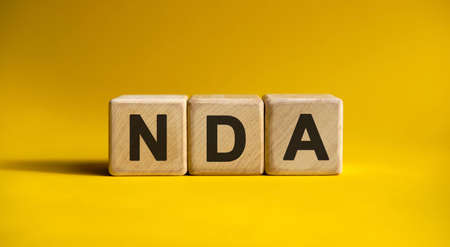 NDA text on a yellow background on wooden cubes