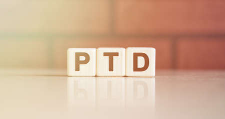 PTD acronym concept. Text on wooden cubes with bright light
