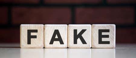 Fake - text on wooden blocks, dark background 版權商用圖片