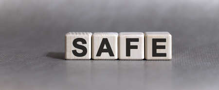 SAFE text on wooden cubes on a monochrome background