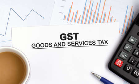 GST - good and service tax document with graphs, diagrams and calculator and a cup of fragrant coffee