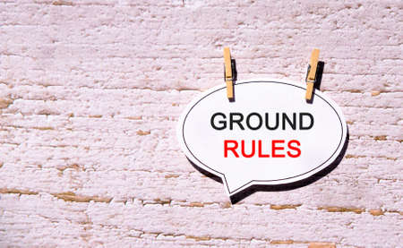 Ground rules on a white sheet with wooden pins
