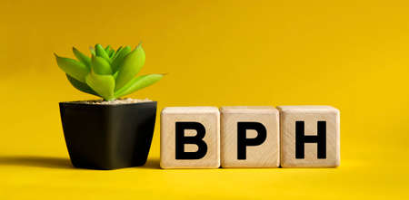 BPH - medical concept on a yellow background. Wooden cubes and flower in a pot. Imagens