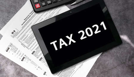 Tax 2021 on a black tablet and with tax forms and calculator
