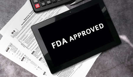 FDA approved on a black tablet and with tax forms and calculator