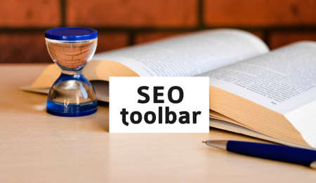 Seo toolbar business concept text on a white background with a hourglass and an open book