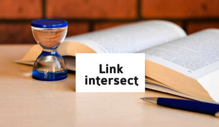 Link intersect - business concept text on a white background with a hourglass and an open book Banco de Imagens