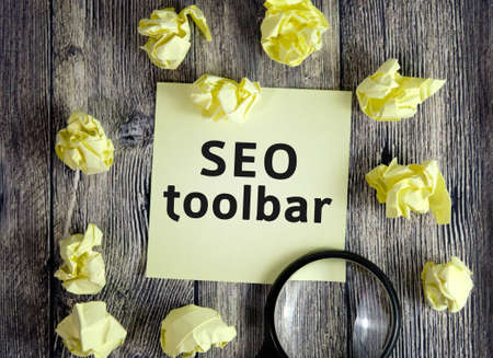 Seo toolbar - text on yellow note sheets on a dark wooden background with crumpled sheets and a magnifying glass Reklamní fotografie