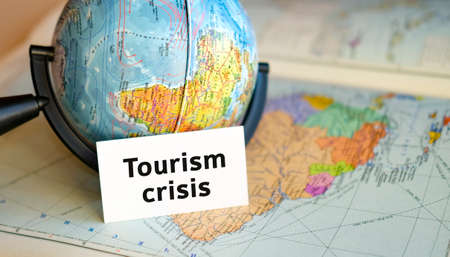 Tourism crisis text on a white sheet on globe on the blue background of the atlas map