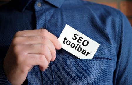 Seo toolbar text on a white sign in the hand of a man in shirt
