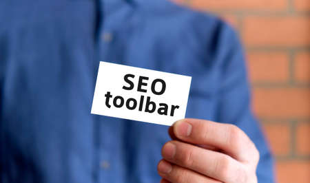 A man in a blue shirt holds a sign with the text of Seo toolbar in one hand