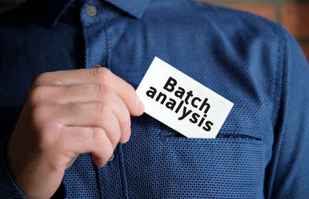 Batch analysis text on a white sign in the hand of a man in shirt