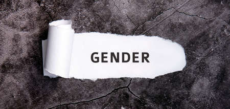 Gender wiht torn white paper on a gray concrete table