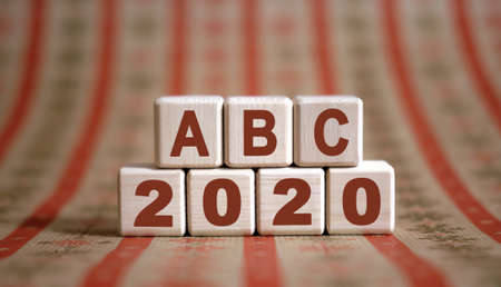 ABC 2020 text on wooden cubes on a monochrome background with reflection.