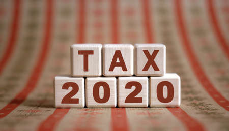 TAX 2020 text on wooden cubes on a monochrome background with reflection.