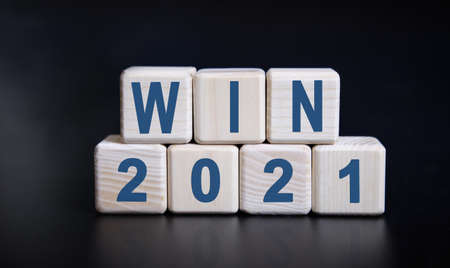 WIN 2021 text on wooden cubes on a black background with reflection. Stock fotó
