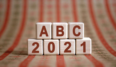 ABC 2021 text on wooden cubes on a monochrome background with reflection.