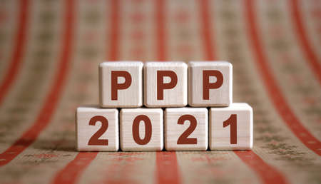 PPP 2021 text on wooden cubes on a monochrome background with reflection. Stock fotó