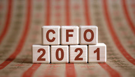 CFO 2021 text on wooden cubes on a monochrome background with reflection.